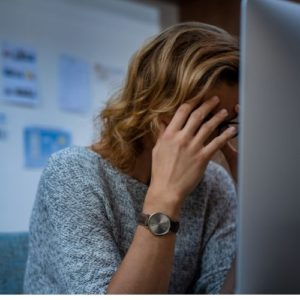 woman with head in hands can't stay productive when stressed