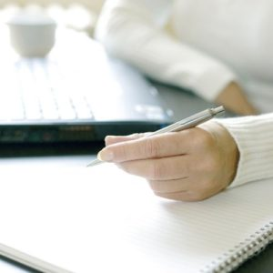 Woman writing work tasks uses the Eisenhower matrix for time management